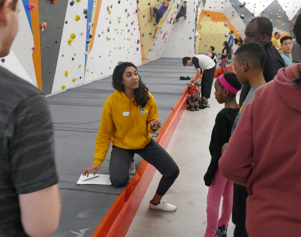 staff member helps family start climbing at gym